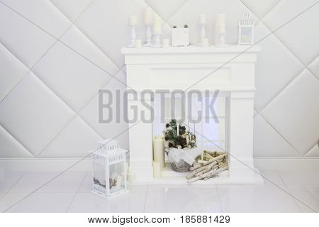 White room with decorative fireplace candles lantern soft walls