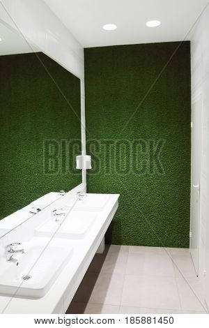 Three white sinks in empty toilet with big mirror and green lawn wall