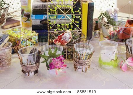 Glasses with decoration (flowers and branches) and books are on table