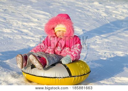 Little girl slides on snowtube down from hill at sunny winter day