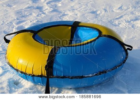 Yellow and blue snowtube is on white snow at winter sunny day