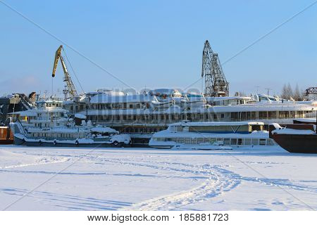 White beautiful passenger ship in frozen river and cranes in winter sunny day