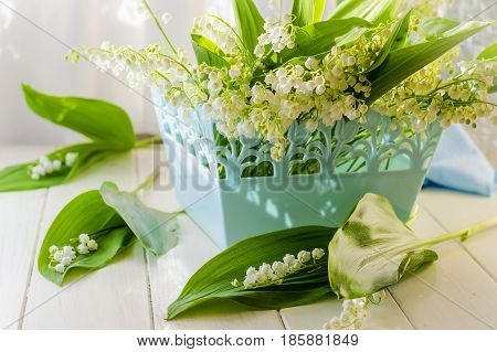 Bouquet of lilies of the valley in a basket on a table by the window