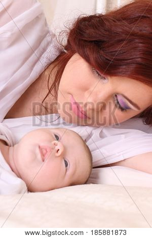 Young mother in a silk white dress lying on the bed with the child and looks lovingly at him focus on mother