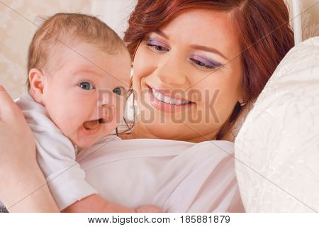 Beautiful young mom that keeps her child in her arms lying on the bed and gently looks at him focus on mother