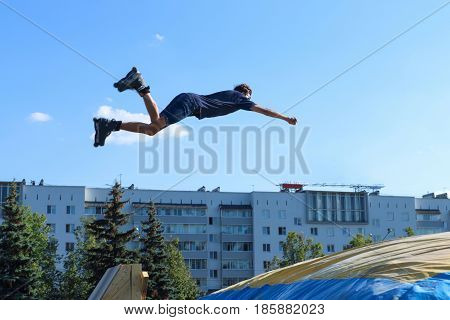Extreme roller in a blue shirt and jeans shorts jumping in aeromat in the Championship of the Perm region.