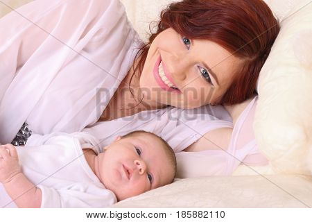 Beautiful young mother lying on the bed with his tiny child and glows with happiness