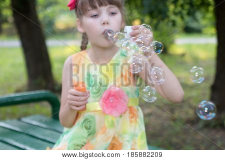 Beautiful little girl in color dress that takes lots of soap bubbles warm day focus on bubbles