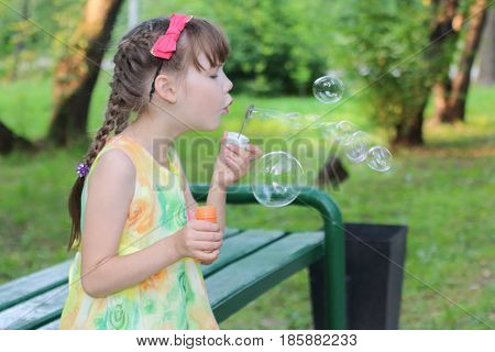 Little girl with pigtails and a cute bow on the head with blow bubbles sitting on the bench