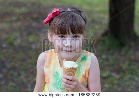 Beautiful little girl in a coloured sundress eating ice cream on a warm summer day