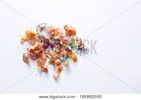Wooden colored pencil sharpening shavings pile on white isolated background, top view, flat lay, copy space