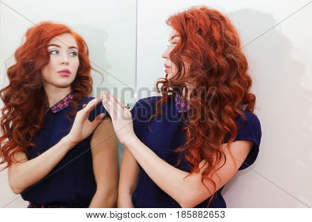 Young woman with beautiful curly hair standing at the mirror and looks at her reflection