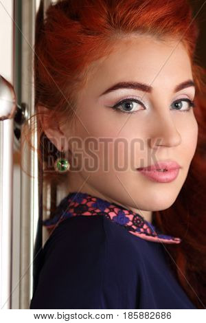 Young woman with beautiful big eyes and professional make-up looks over the shoulder