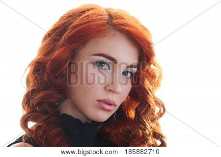 Charming young woman with beautiful curly red hair on a white background looking forward