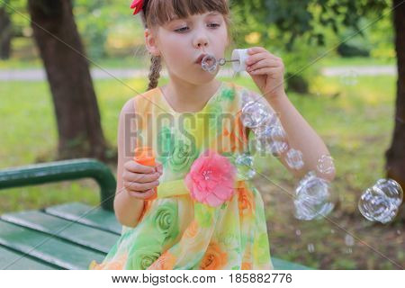 Little girl in beautiful colored dress sitting on a bench and blow bubbles