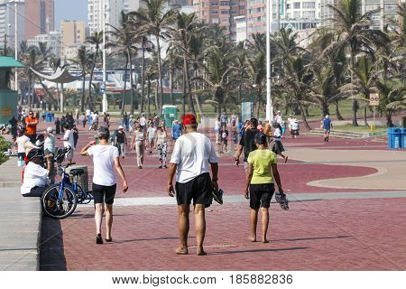 People Walking On Early Morning  Beachfront Paved Promenade