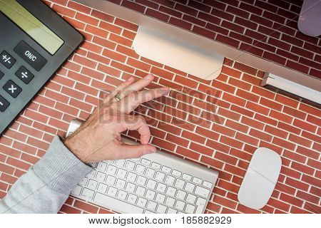 top view of a man working in office with everything OK gesture and with modern technology on red brick background