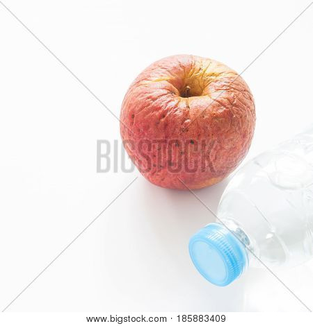 Health care concept with spoiled apple and bottle of water on white background