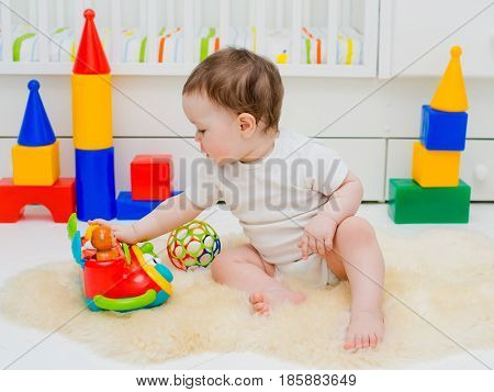 Child 6 months playing on the floor in the room