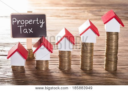 House Models On Increasing Coin Stacked With Property Tax On Chalk Board