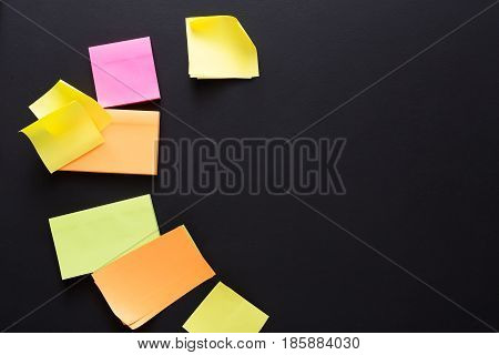 School stationery background, memo sticky notes on black board, top view.