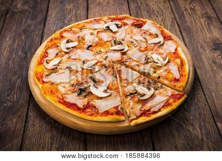 Pizza with mushrooms and smoked chicken meat - thin pastry crust isolated at wooden background, with piece cut off