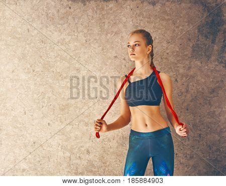 Healthy lifestyle and sport concepts. Woman in fashionable sportswear is doing exercise with skipping rope.