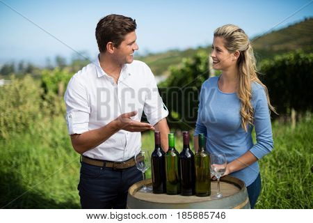 Smiling friends standing by wine bottles on berrel at vineyard