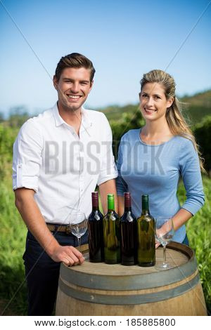 Portrait of happy friends standing by wine bottles on berrel against clear blue sky at vineyard