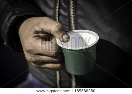 Dirty Beggar Hand Holding Plastic Cup. Poor Man Begging For Money On The Street Close Up.