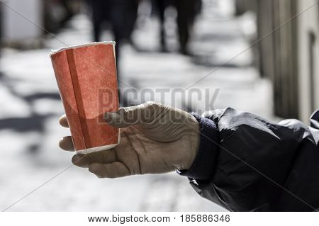 Poor Man Begging For Money On The Street Close Up. Dirty Beggar Hand Holding Paper Cup
