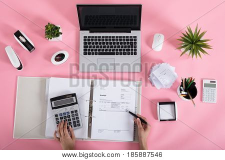 Elevated View Of A Businesswoman Calculating Tax Using Calculator On Pink Desk