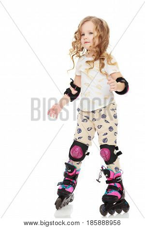 Beautiful, chubby little girl with long, blond, curly hair. Girl riding roller skates in protective gear. Isolated on white background.
