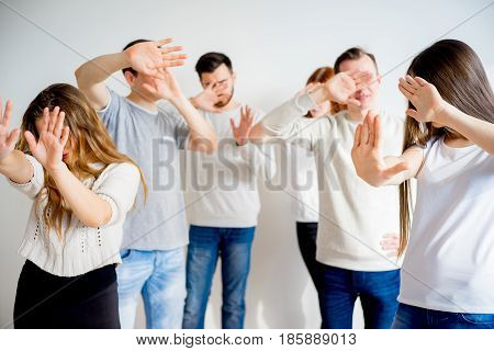 Group of people hiding their faces with hands
