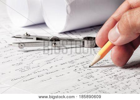 Closeup of a Hand Working with Mathematics Formulas