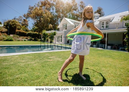 Full length shot of cute little girl playing with hula hoop in the backyard. Young girl playing outdoors on a summer day.