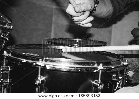 Hand of drummer with sticks and drums, close-up black and white