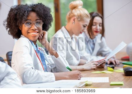 Portrait of a beautiful african medic student sitting with classmates at the desk during the lesson