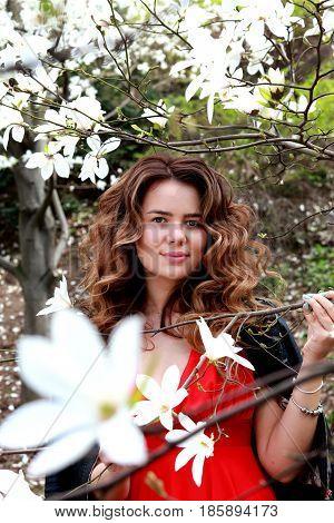 Beautiful girl near magnolia tree. Head portrait of beautiful woman with magnolia flowers