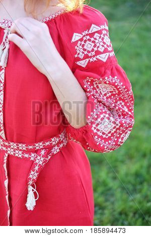 Detail of traditional Ukrainian costume vyshyvanka dress made of red linen fabric and white cross stitch pattern