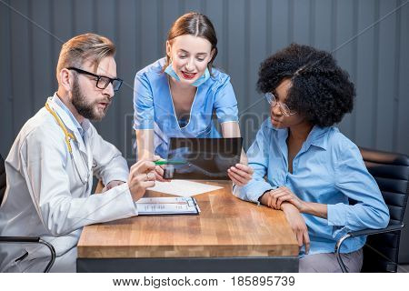 Young afro ethnicity woman having a medic consultation sitting with doctor and nurse at the office