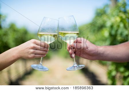 Cropped hands of couple toasting wineglasses at vineyard