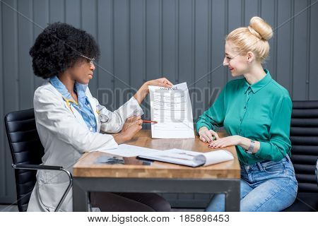 Female doctor showing insurance document to the woman patient at the office