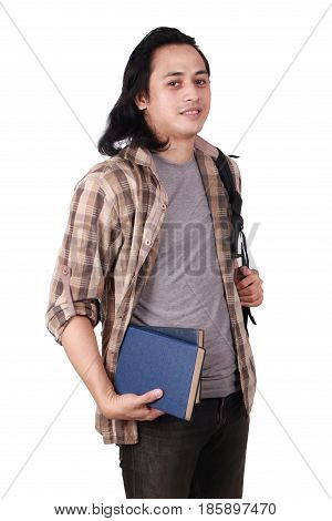 Photo image portrait of a cute young Asian male student with long hair looking to camera standing and smiling while holding books half body portrait isolated on white