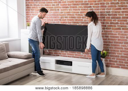 Smiling Young Couple Carrying New Television At Home