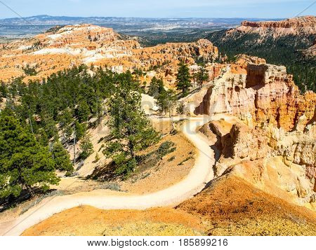 Sunny day in Bryce Canyon, Utah, USA. Dusty country road in rocky valley with green trees.