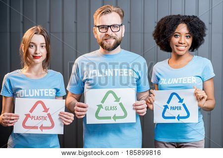Portrait of three multi ethnic volunteers holding signs of sorting waste standing indoors on the gray wall background