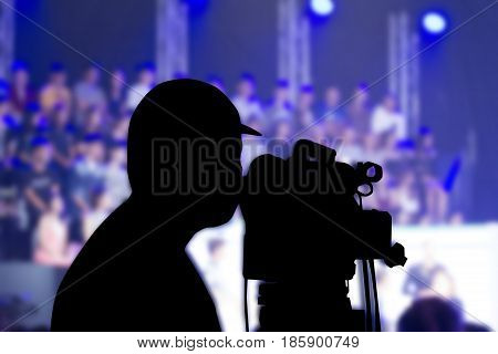 Silhouette image of the cameraman working on blurry background in television studio