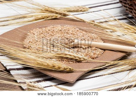 Bamboo plate and wooden spoon filled with wheat bran surrounded by wheat ears. Dietary supplement to improve digestion. Source of dietary fiber