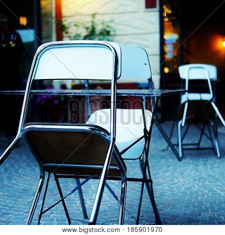 an empty couple of tables with chairs in a bistrot near the city centre of rome